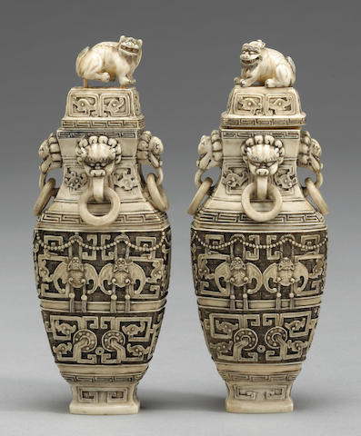 A pair of carved and reticulated ivory vases with ring handles and Qilin finials