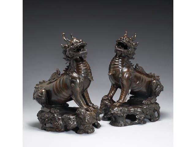 A pair of cast bronze qilong form censers, Late 20th Century