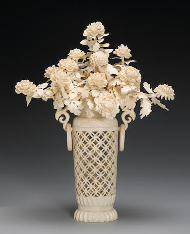 An impressive and large Chinese carved and reticulated ivory vase holding chrysanthemum, third quarter 20th century