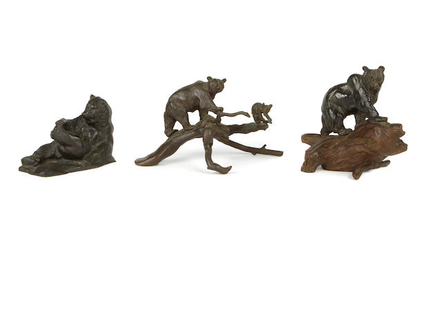 A group of three patinated bronze sculptures of bears, one on wood stand