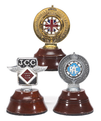 A collection of early car badges,