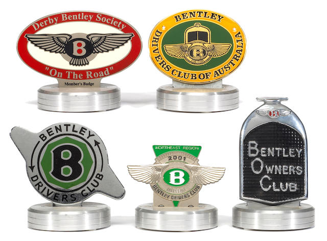 An assortment of Bentley Drivers Club badges,