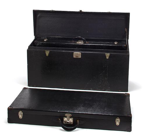 A black motoring trunk with two suitcases,