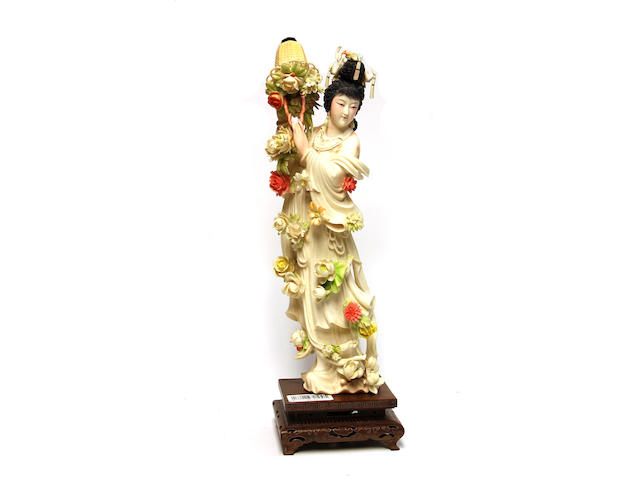 A large carved ivory Chinese maiden, ona pedestal base, holding a basket of flowers to her shoulders, mid to late 20