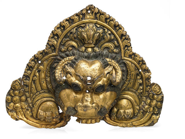A Gilt copper alloy repoussé kirttimukhara shrine element Tibet, 16th-18th century