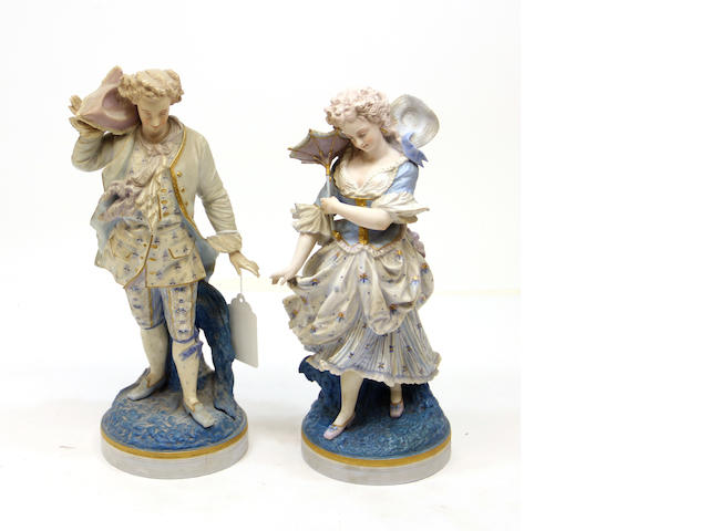 A pair of German bisque figures of a man and woman in 18th century costume