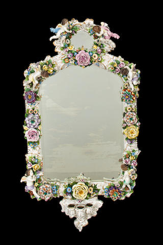 A German glazed porcelain floral and putti encrusted mirrored sconce second half 19th century