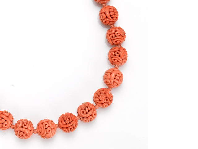 A carved coral bead and gold-plated necklace