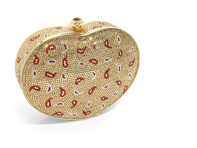 A gold rhinestone heart purse with red and white paisley motifs and a tiger's eye closure,