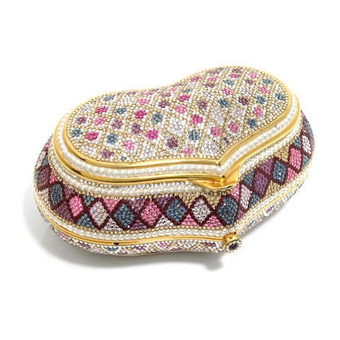 A heart shaped purse with multi-colored flower and diamond geometric motifs and pearl bead detailing, accompanied with a pouch and outer box