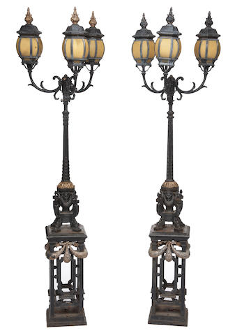 A pair of Neoclassical style parcel gilt and painted cast iron and glass three light torchères possibly American late 19th century
