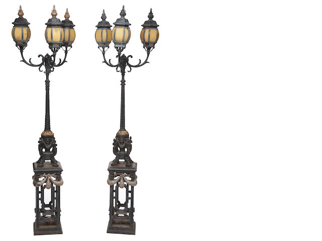 A pair of Neoclassical style parcel gilt and painted cast iron and glass three light torcheres<br>possibly American<br>late 19th century