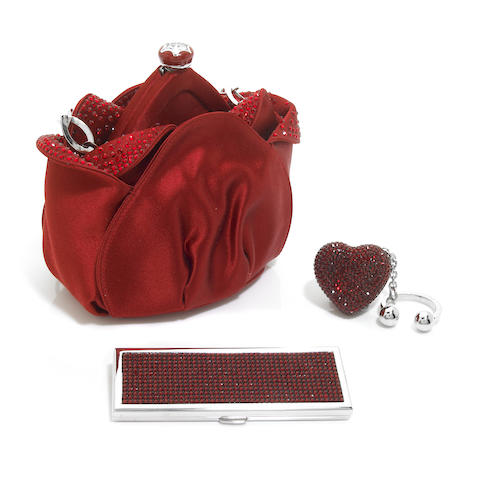 A crimson colored satin and crystal tulip purse together with a crystal heart keychain and a rectangular double-sided mirror,