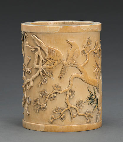A carved and tinted ivory brush pot with bird and flower decoration Late 19th century