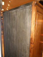 A Chinese tall mixed wood two-door cabinet with carved and reticulated panels to the doors