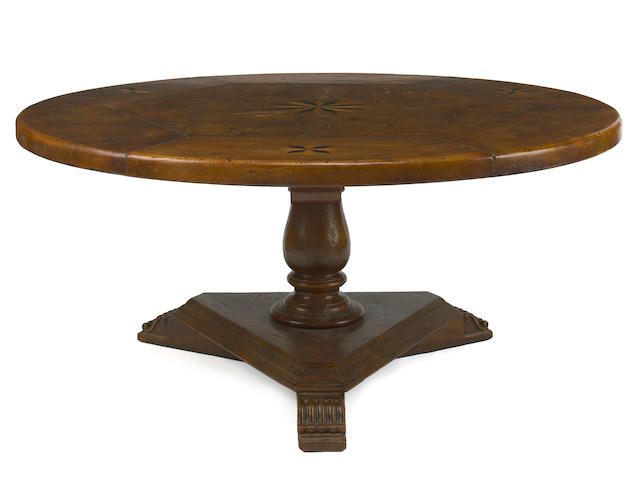 An Italian Baroque style walnut and elm circular dining table
