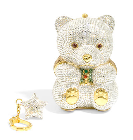 A silver crystal bear minaudiere with a green and gold crystal jacket together with a silver crystal star keychain,