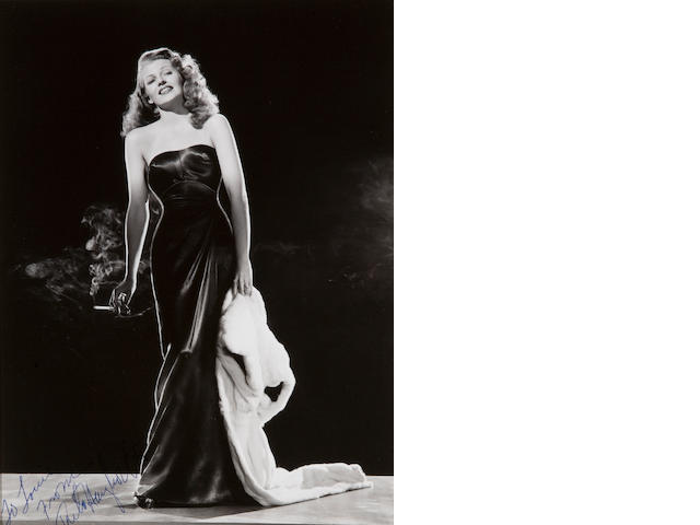 Signed photo of Rita Hayworth 8 x 10. Gilda. Standing on boulder.