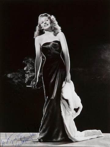 Signed photo of Rita Hayworth 8 x 10. Gilda. Standing on boulder.