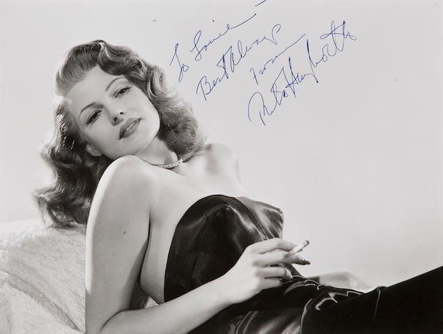 Signed photo of Rita Hayworth 8 x 10. Gilda. Lying on boulder.