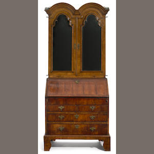 A Queen Anne featherbanded walnut double domed top secretary bookcase . first quarter 18th century