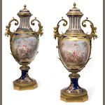 An imposing pair of Sèvres style gilt bronze mounted covered urns <BR />late 19th century