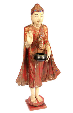 A lacquered and mirror inlaid wood standing figure of Buddha