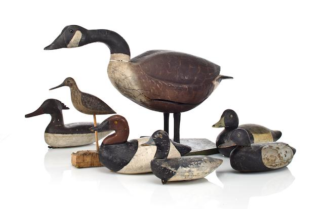 Seven painted wood duck decoys, including ducks, a goose and shore bird