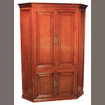 A George III style mixed wood corner cupboard