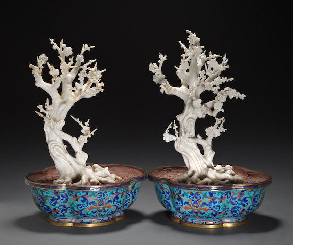 A pair of Dehua porcelain flowering trees in Canton enameled metal planters Late Qing dynasty