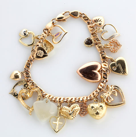 A 14k gold charm bracelet suspending eighteen gem-set, 14k and 10k gold heart motif charms