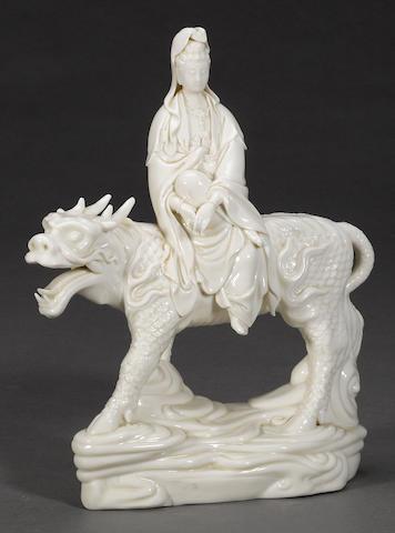 A Dehua porcelain figure of Guanyin atop a fabulous beast Jiaqing mark