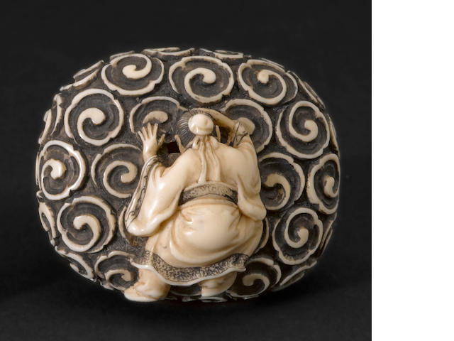 A stained ivory manju nestuke By Keiun (Omura Minosuke, b. 1912)