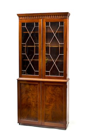George III c. 1810 bookcase or display cabinet, English.  Mahogany with ebony stringing.  Upper part with astragal glazed doors and lancet molded cornice, the lower with finely figured and inlaid doors.