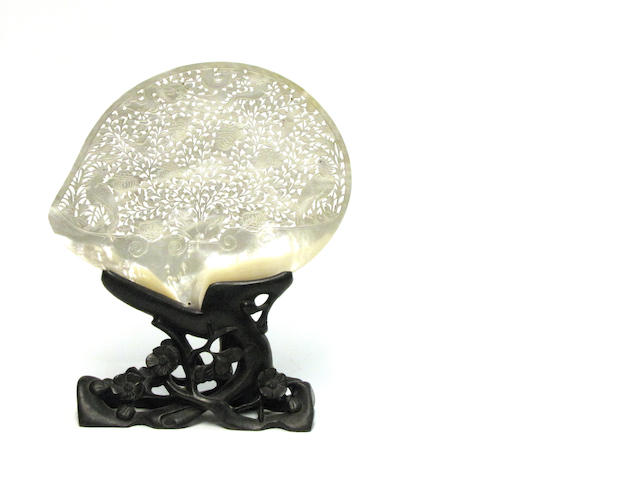 A reticulated  mother-of-pearl shell on a wood stand Late Qing/Republic Period Late Qing/Republic Period