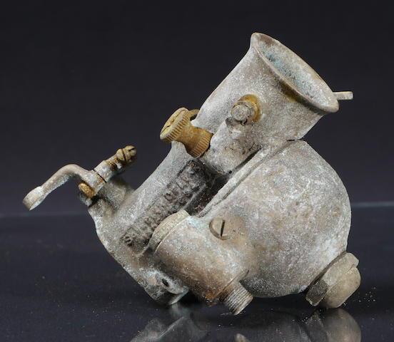 A bronze Schebler Deluxe carburetor,