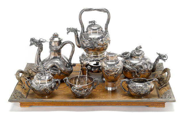 A Japanese export silver six-piece tea and coffee set together with silver tongs, a silver tea caddy and a silver mounted wood tray<BR>Meiji/Taisho period, arks possibly reading Samurai Shokai in Japanese<BR>(water kettle with damage to handle and loss of wick pot to heater, silver tea caddy lacking interior cover) [9]