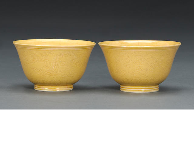 A pair of yellow glazed porcelain bowls, Daoguang mark, one repaired