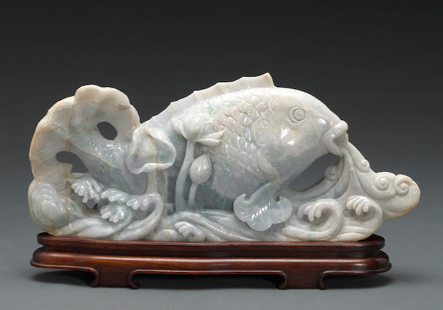 A large jadeite carving of a carp and lotus on waves