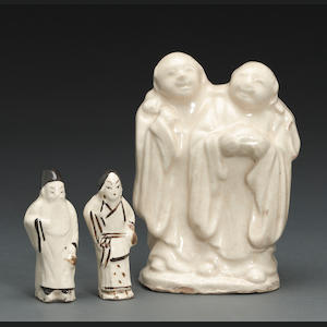 A white glazed ceramic group of the Hehe Twins, together with two small Cizhou figures