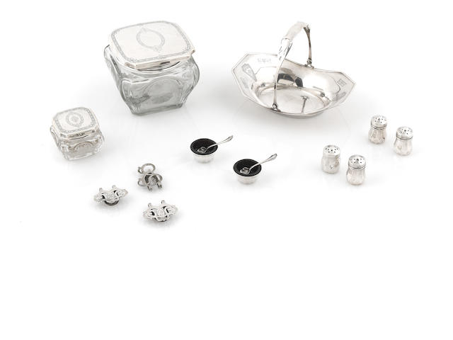An assembled group of sterling silver and silver mounted table ware and vanity articles, including a basket, mugs, a vase, vanity boxes, salt cellars, pepper casters and money clips