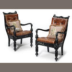 A pair of Anglo-Indian style carved ebonized library armchairs