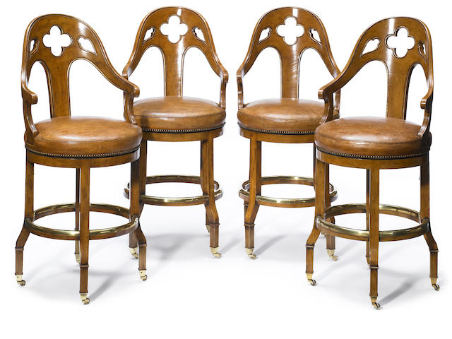 A set of four Gothic Revival mixed wood revolving bar stools