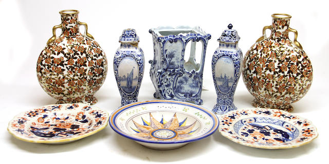 An assembled group of European ceramics – comprising a pair of English two handled moon flasks, a pair of English ironstone plates, a French faience plate with sunburst motif, a Dutch Delft blue and white sedan chair, and a Dutch Delft pair of vases 19th century