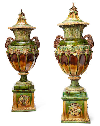 An imposing pair of Continental glazed earthenware covered urns on pedestals