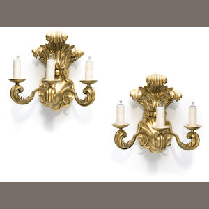 A pair of Rococo style gilt bronze and carved giltwood three light wall sconces