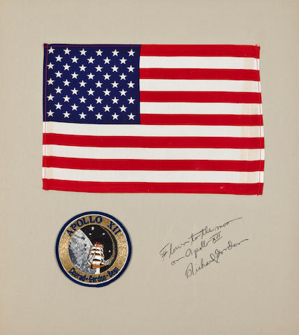 LARGE FLAG CARRIED TO THE LUNAR SURFACE ON APOLLO 12. Flown United States flag, silk, 8 x 11½ inches.  Mounted on a 20 x16 inch mat board with a 4 inch diameter Apollo 12 crew emblem.