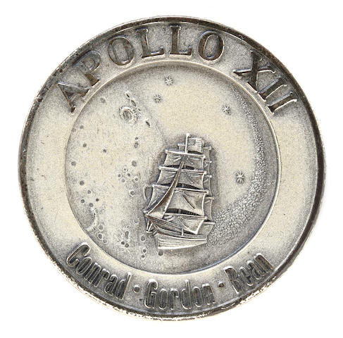 "COOPER'S FLOWN APOLLO 12 ROBBINS MEDALLION. A GIFT FROM ""PETE."" Flown Apollo 12 Robbins medallion, sterling silver, 1¼ inches in diameter. The crew mission emblem is on the obverse with the mission dates and serial number 147 on the reverse."