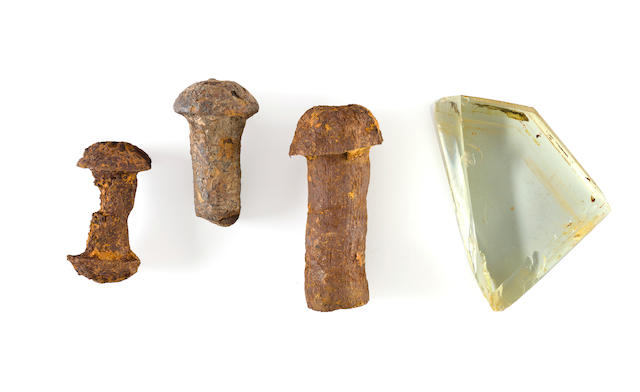 [TITANIC WRECK] Three rivets and one piece of porthole glass  circa 1911 3-1/2 in. (8.9 cm.) long (the largest rivet); 2-3/4 x 3-3/4 in. (7 x 10 cm.) (the piece of glass) 4