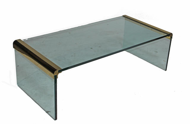 A contemporary brass and glass coffee table